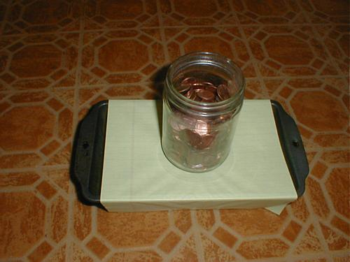 penny jar on paper stretched across loaf pan